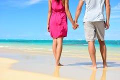Strandpaar in de handen van de liefdeholding op wittebroodsweken royalty-vrije stock afbeelding