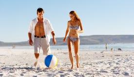 Strandpaare, die mit Kugel spielen Lizenzfreies Stockfoto