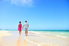 Strandpaarhändchenhalten, das auf Flitterwochen geht Stockfotografie