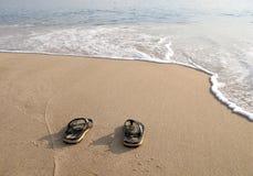 Strandpantoffels in het zand op strand stock afbeeldingen