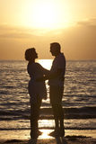 strandpar man den höga solnedgångkvinnan Arkivfoton