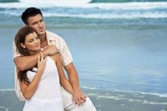 strandpar omfamnar manromantikerkvinnan Royaltyfri Bild