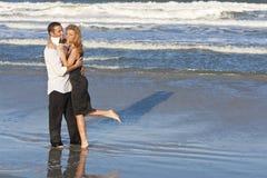 strandpar omfamnar manromantikerkvinnan Arkivfoton