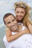strandpar omfamnar manromantikerkvinnan Arkivbilder
