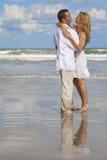 strandpar omfamnar romantiskt barn Arkivfoto