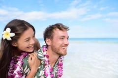 Strandpar som har det roliga piggybacking Hawaii loppet royaltyfria bilder