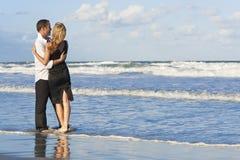 strandpar som omfamnar gyckel som har Royaltyfri Fotografi