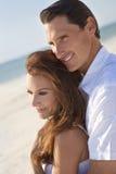 strandpar som omfamnar romantiker royaltyfri foto