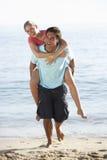 strandpar som på ryggen tycker om barn för ferie arkivfoto