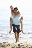 strandpar som på ryggen tycker om barn för ferie fotografering för bildbyråer