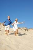 strandpar som tycker om den running pensionären för ferie Fotografering för Bildbyråer