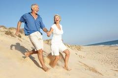 strandpar som tycker om den running pensionären för ferie Arkivfoton