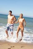 strandpar som tycker om feriebarn Fotografering för Bildbyråer