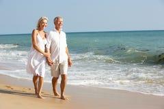 strandpar som tycker om feriepensionärsunen Royaltyfria Bilder