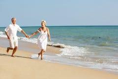 strandpar som tycker om feriepensionärsunen Royaltyfri Fotografi