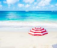 Strandparaplu door de oceaan Stock Afbeelding