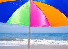 Strandparaplu door de oceaan Stock Afbeeldingen