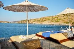 Strandparaplu en bedden Stock Afbeelding