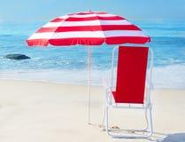 Strandparaplu en stoel door de oceaan Stock Afbeeldingen