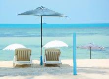 Strandparaplu en strandbed met zonnescherm bij kust Royalty-vrije Stock Foto's