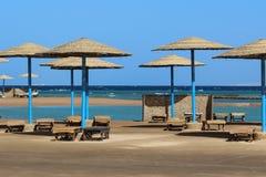 Strandparaplu's en ligstoelen stock afbeelding