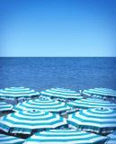 Strandparaplu's en overzees Stock Fotografie