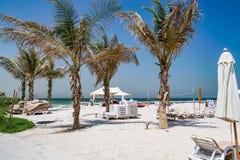 Strandparaplu's en wit zandstrand De Emiraat van Ajman De zomer van 2016 Royalty-vrije Stock Foto