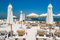 Strandparaplu's en wit zandstrand De Emiraat van Ajman De zomer van 2016 Stock Afbeeldingen