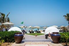 Strandparaplu's en wit zandstrand De Emiraat van Ajman De zomer van 2016 Stock Fotografie