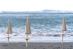Strandparaplu's tegen de achtergrond van sterke golven stock afbeeldingen