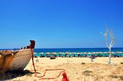 Strandparaplu's, wit vergoelijkt boom en deel van boot mooi landschap in zonnige de zomerdag op Naxos-eiland royalty-vrije stock fotografie
