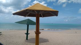 Strandparaplu's, zand en turkoois water Stock Afbeeldingen