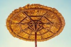 Strandparaplu van stro tegen de blauwe hemel wordt gemaakt die royalty-vrije stock afbeelding