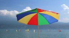 Strandparaply i regnbågefärger och grupp av surfare på gar Arkivbild