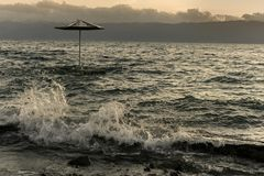 Strandparaply i sjön Ohrid på solnedgången för stormigt väder Royaltyfria Foton
