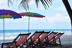 Strandparaply och stol royaltyfri foto