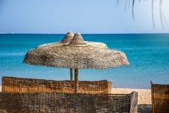 Strandparaply som stickas med träpinnar som ger naturlig skugga royaltyfria foton