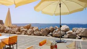Strandparaplyer över tabeller i ett kafé på en stenig kustlinje mot havet och himlen Royaltyfri Fotografi