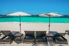 Strandparaplyer och dagdrivare på den perfekta vita stranden Royaltyfri Foto