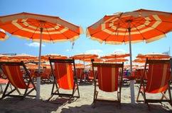 Strandparaplyer och stolar på den härliga stranden i Marina di Pisa, Italien Royaltyfria Bilder