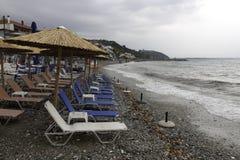 Strandparaplyer och tomma vardagsrumstolar på en molnig dag Platamonas arkivfoto
