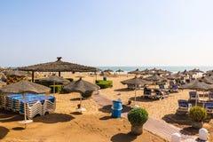 Strandparaplyer på den sandiga stranden Royaltyfri Bild