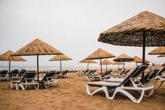 Strandparaplyer på den sandiga stranden Arkivfoton