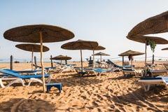 Strandparaplyer på den sandiga stranden Arkivbilder