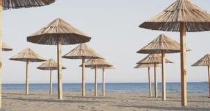 Strandparaplyer på den sandiga stranden på solnedgången arkivfilmer