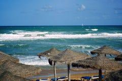 Strandparaplyer på den sandiga stranden vid havet Arkivbilder