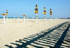 Strandparaplyer på en tom strand Arkivbild