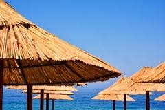 Strandparaplyet som göras av, gömma i handflatan blad på bakgrunden av en exotisk strand i Montenegro tropisk bakgrund royaltyfri bild