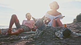 strandpargyckel som har barn Helg på ön Barnet kopplar ihop att sjunga med en gitarr på stranden deras roligt arkivfilmer