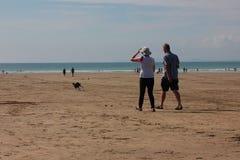 Strandplats med ett par som går Augusti 2018 royaltyfri fotografi
